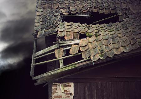 derrumbe: Techo de madera vieja en el colapso de edificio en mal humor oscuro cielo de la tarde