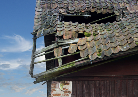 damaged roof: Old wooden roof on collapsing building on blye bright sky