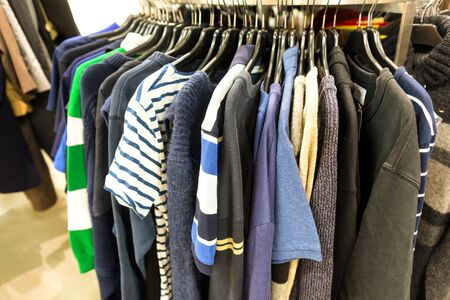 second hand: Sweaters and t-shirts on rack for sale in second hand store