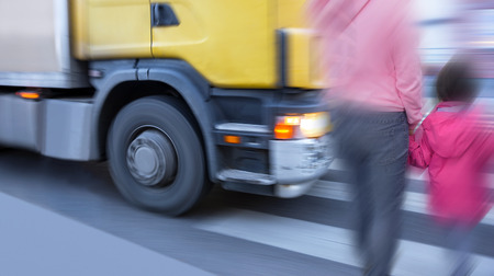 crossing: Mother and daughter on pedestrian crossing when big truck is passing Stock Photo