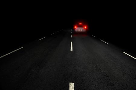 dark red: Dark asphalt road and car with red rear lights