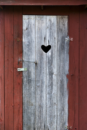 latrine: Door with heart on old wooden outdoor traditional Swedish toilet in countryside