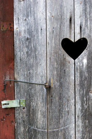 latrine: Close up of door with heart on old wooden outdoor traditional Swedish toilet in countryside