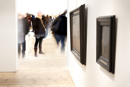exhibition crowd: Two vintage picture frames on wall in art museum, with crowd of visitors in blurred motion in background
