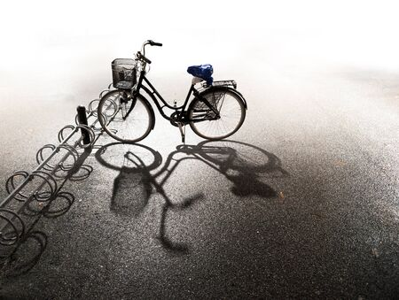 parked bicycles: Bike with basket parked in bicycle rack with bright background and shadow on asphalt on autumn evening