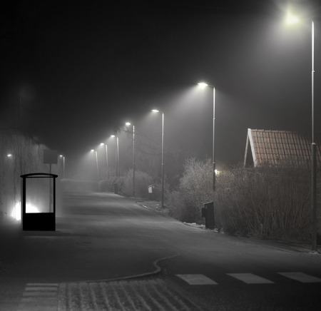 bus stop: Empty bus shelter in suburban area on dark foggy evening