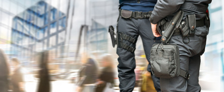 threats: Armed policemen on guard in busy street with modern glass buildings and people walking Stock Photo