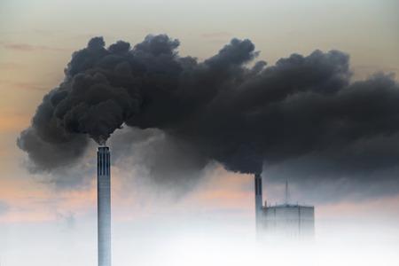 Dark smoke from chimneys of power plant on orange sky