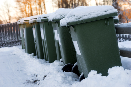 disposed: Green garbage cans in a row with snow on top on cold winter day with orange sunlight in background