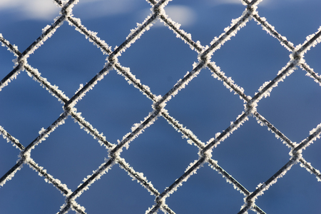 chain link fence: Chain link fence with snow crystals on blue sky