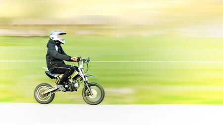 young boys: Young man on small motorbike or moped in blurred motion