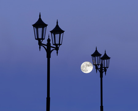 full moon romantic night: Two traditional lamp posts on purple sky with full moon