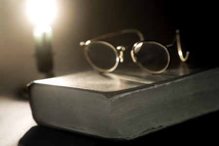 lit candle: Ancient book lit by candle and old glasses on top Stock Photo