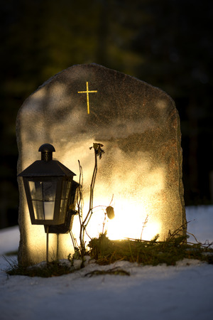 graves: tombstone in winter reflecting evening light