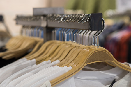retail display: White t-shirts on hangers for sale in store Stock Photo