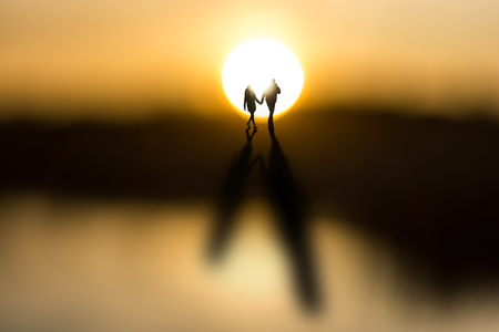 couple lit: Young couple holding hands, back lit by sun at dawn, casting long shadows