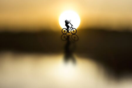 packer: silhouette of cyclist with rucksack on beautiful sunset
