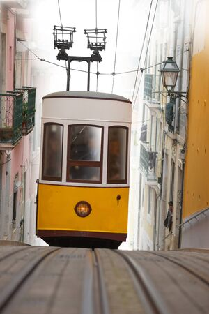 Yellow tram on narrow street on a steep hill in the beautiful city of Lisbon Zdjęcie Seryjne