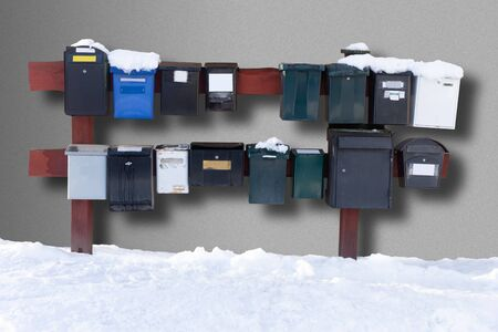 Row of traditional letter boxes in winter, casting shadow on concrete wall