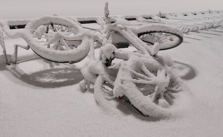 Two bicycles in a heap, covered in snow by bicycle stand Imagens