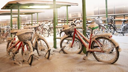 Red bike in bicycle park during snow storm Imagens
