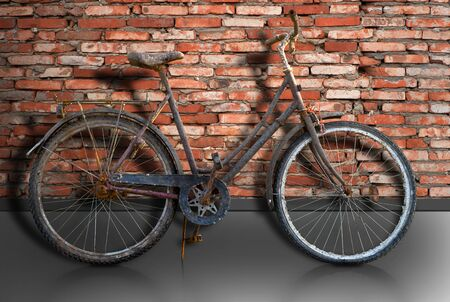 Rusty bike parked by brick wall, with reflection in street