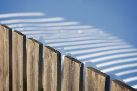 Wooden fence casting shadow on untouched snow