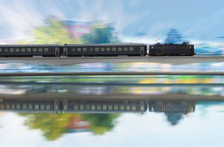 Traditional long distance train on railway bridge, in blurred motion with reflection in water