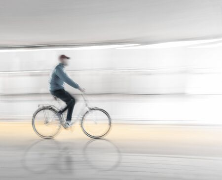 Man in blurred motion cycling along wet road with reflection in street