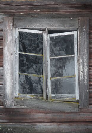 Ancient weathered window in bad condition, with hand made glass in wooden frame on worn wooden wall