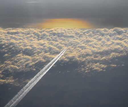 High angle view of passenger aircraft with vapour above the clouds at sunset
