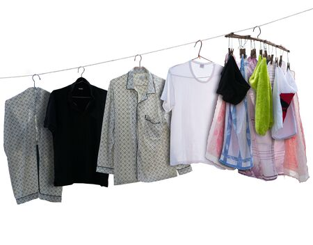 washed shirts and towels with coat hangers hanging to dry on clothesline, isolated on white