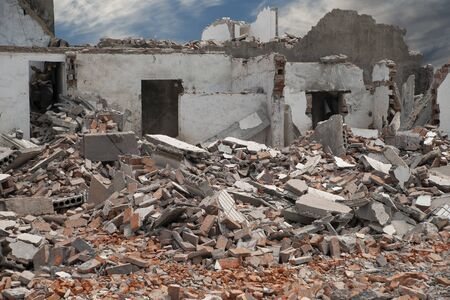 Demolishing site with ruined house and heap with bricks and other debris.