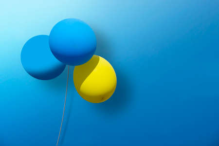 Sparse 3d design with blue and yellow balLoons on blue background.   Copy space, can be used as greeting card.