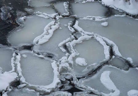 Iee floes with rim of snow in dark river