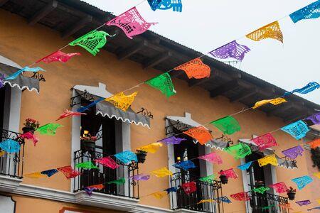 许多颜色的剪纸或纸picado在一个小镇的街道在墨西哥