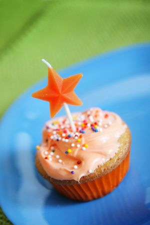 orange cup cake with candle photo