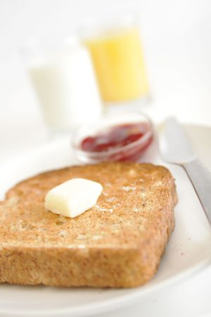 toast with butter a glass of milk and orange juice in background 版權商用圖片