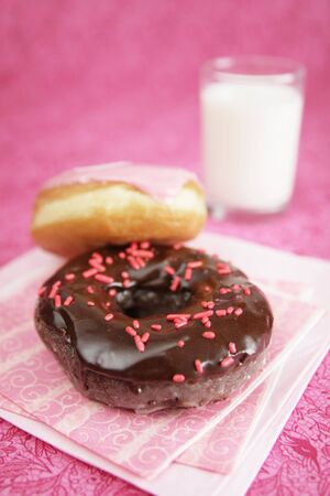 Chocolate and vanilla donut on pink background photo