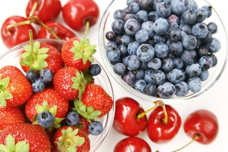 Close up of fresh fruits, strawberry, blueberry and cherry on a white background photo