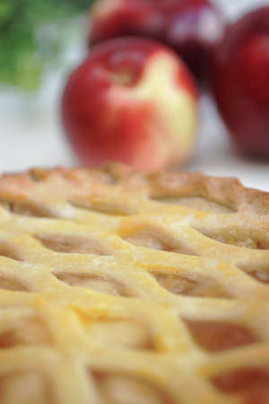 Warm apple pie with fresh red apples in background photo