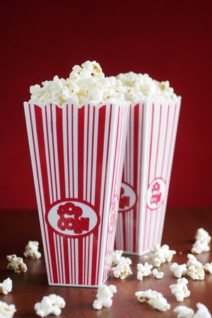 Two pop corn container full of pop corn on red background 스톡 콘텐츠