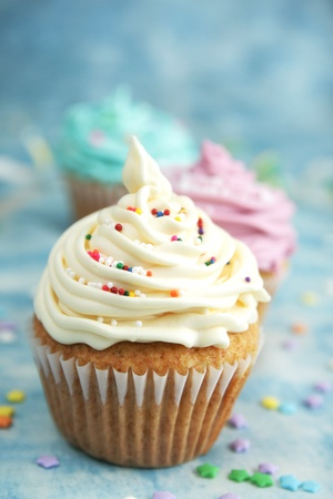 cup: Vanilla cup cake with white icing and candies on top