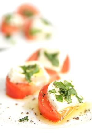 appetizers menu: Tomato slice with cheese and fresh basil on top