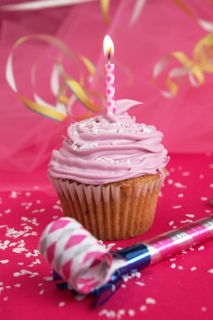 Pink cup cake with candle and party blower on fushia background photo