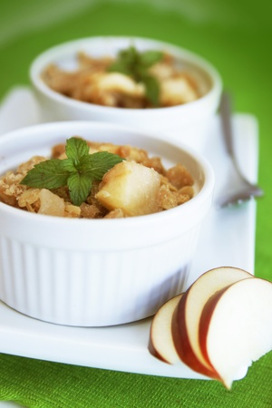 Home made apple crumble in a white container on a green background Banco de Imagens - 8338325