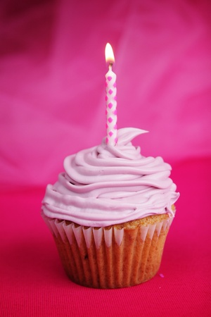 Pink cup cake with candle on fushia background photo