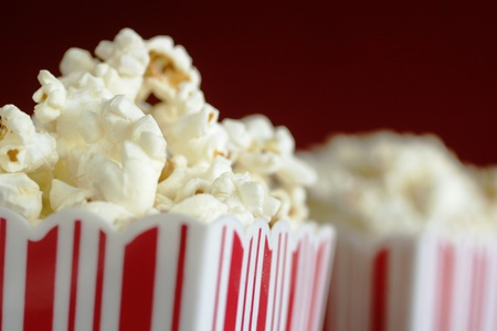 movie theatre: Close up of a container full of pop corn with a second one in background