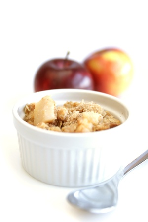 Home made apple crumble in white container with spoon and red apples in background