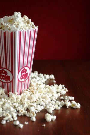 popcorn: Contenitore pieno di pop corn e pochi in una tabella Archivio Fotografico